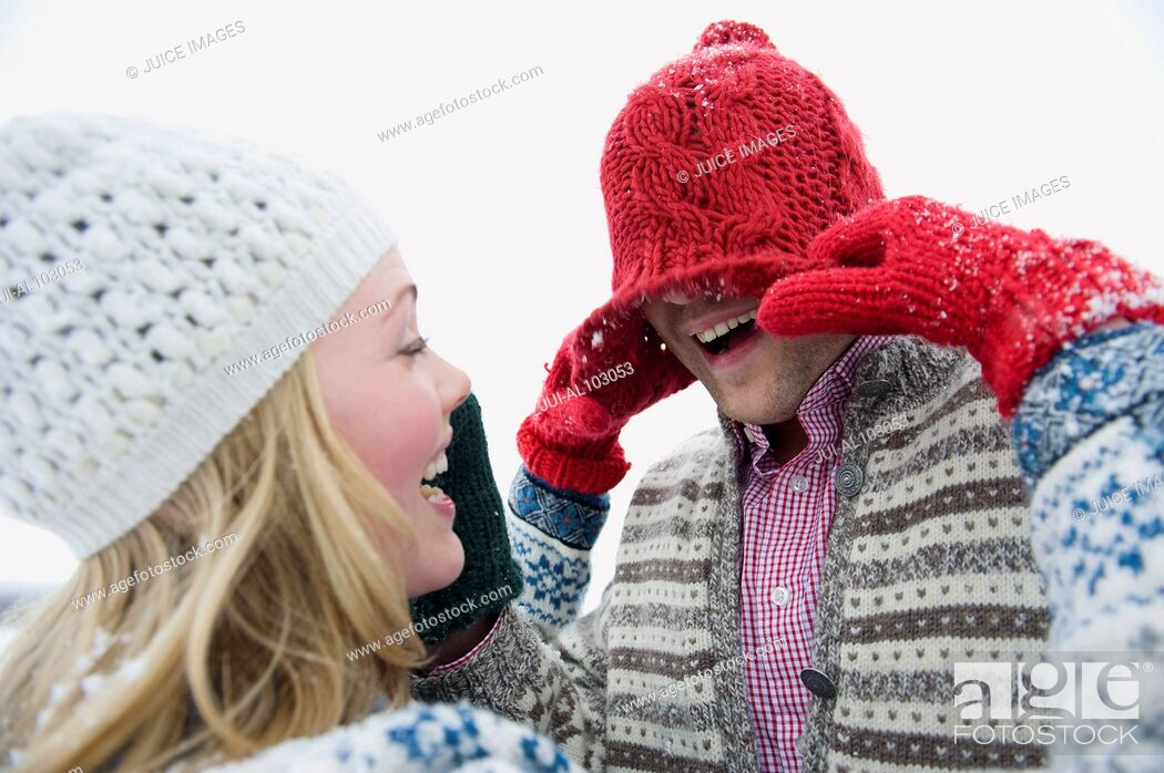 Imagen: A young couple wearing woolen hats playing in the snow.