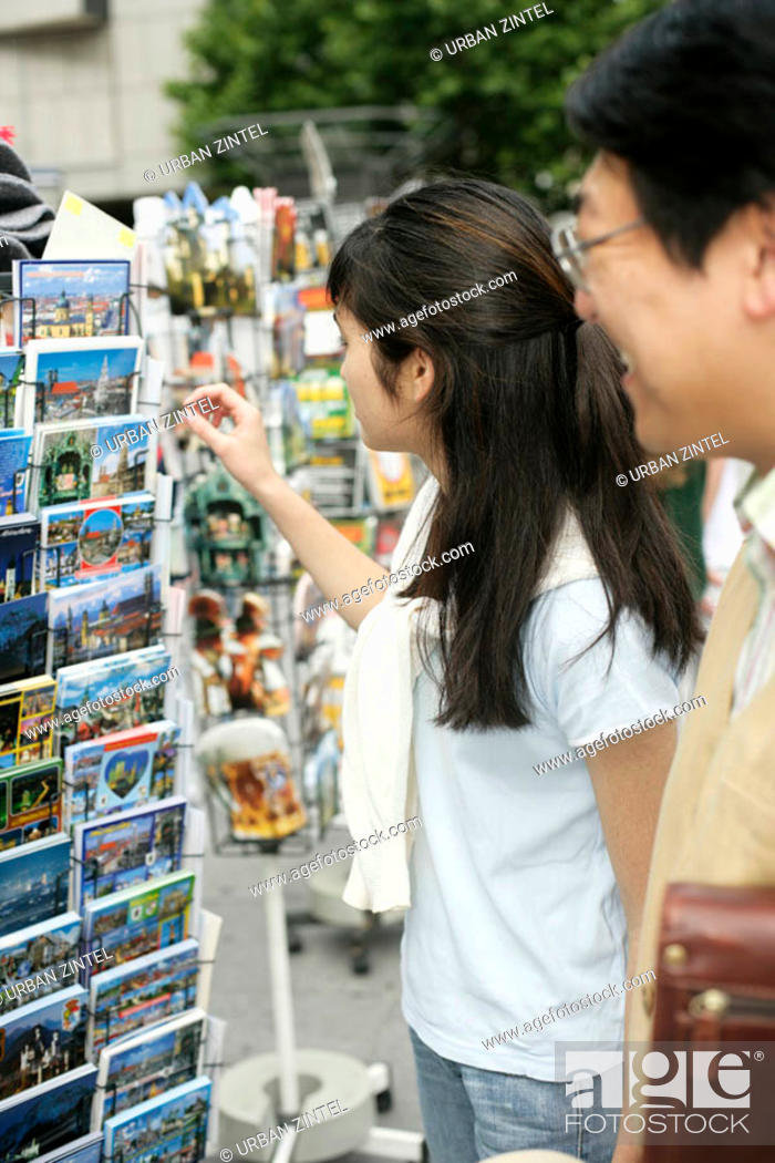 Stock Photo: Young Asian woman next to a man grasping a postcard from a rack, selective focus.