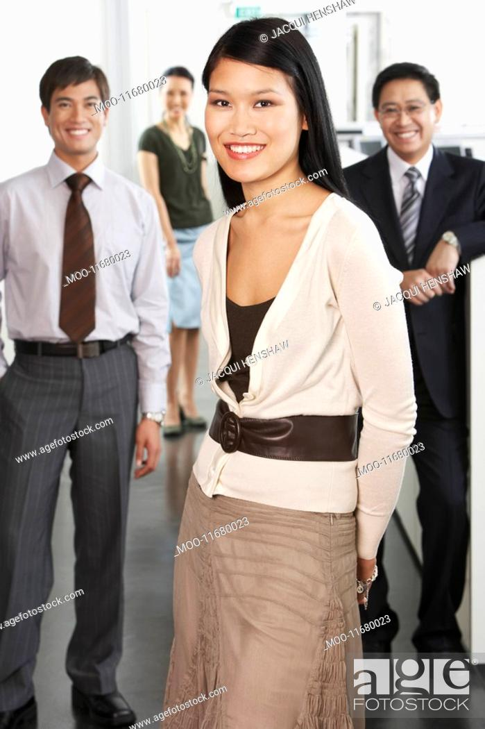 Stock Photo: Business woman standing in front of colleagues in office portrait.