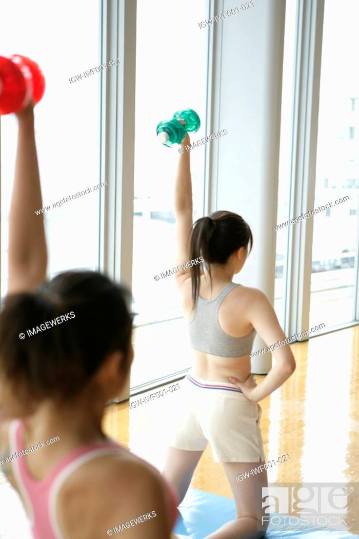 Stock Photo: Two young women lift dumbbells as they Workout in the gym.