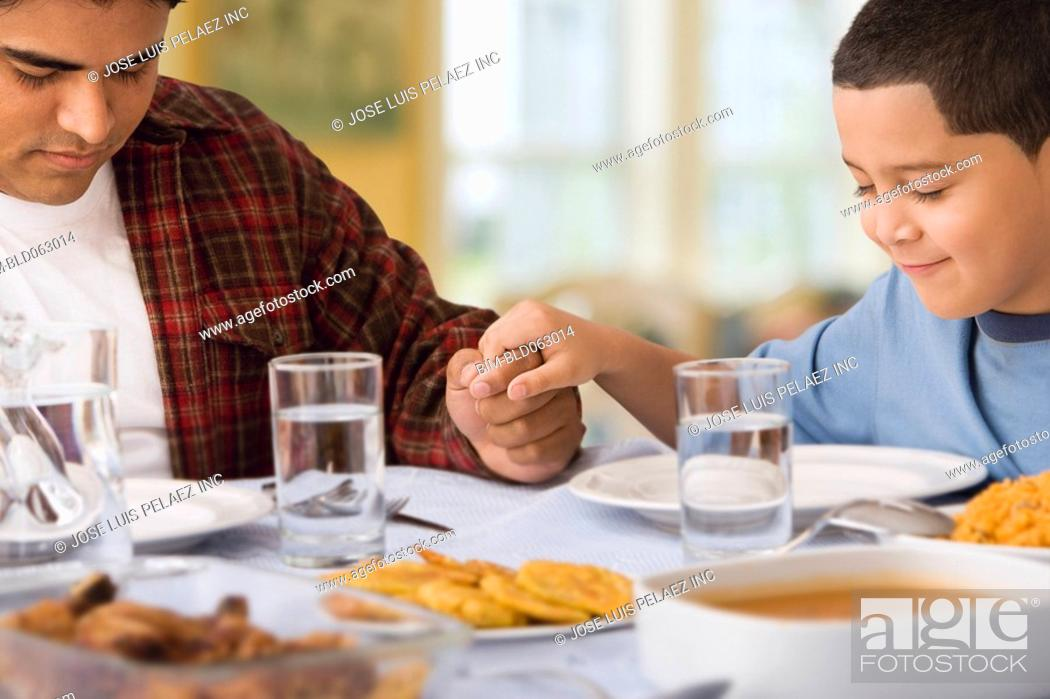 Stock Photo: Hispanic father and son praying at dinner table.