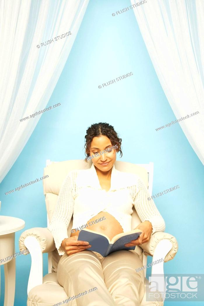 Stock Photo: Pregnant Mixed Race woman reading book.