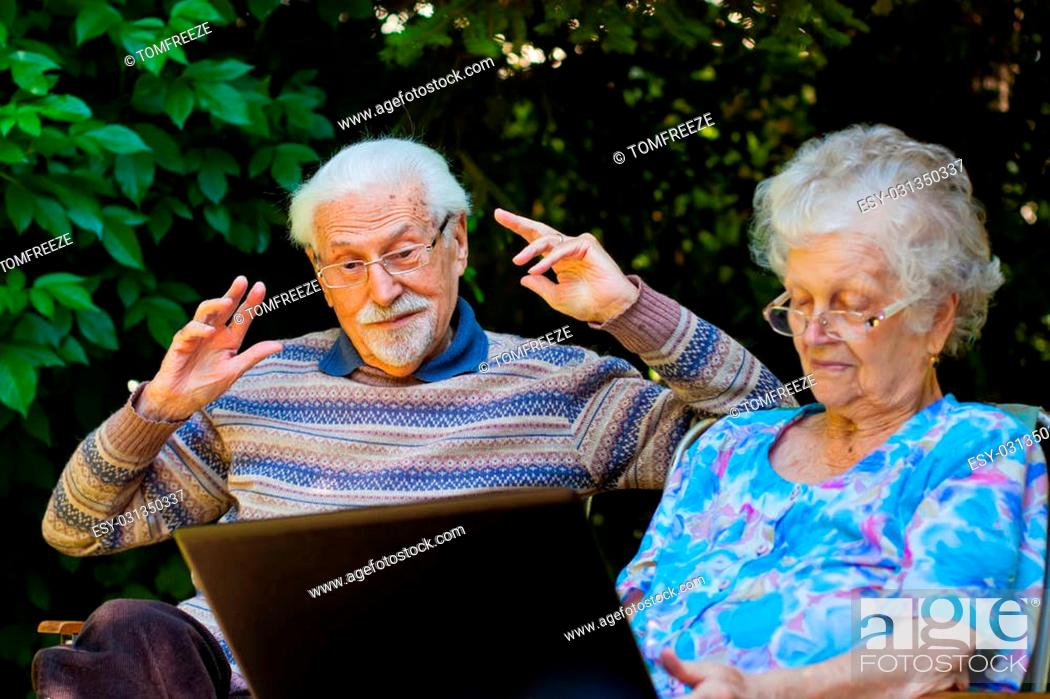An Elderly Couple Having Fun With The Laptop In The Garden