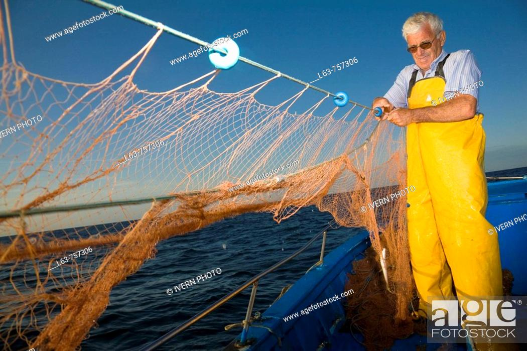 Stock Photo: Senior fisherman fishing with nets in his boat, Cambrils. Tarragona province, Catalonia, Spain.