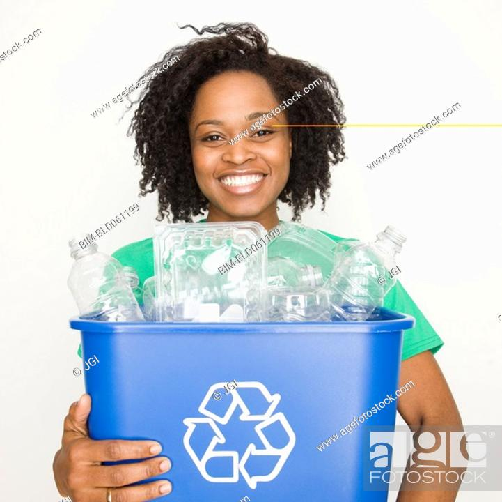 Stock Photo: African woman holding recycling bin.