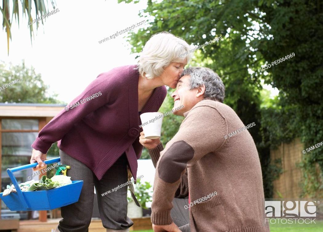 Stock Photo: Senior woman kissing husband.