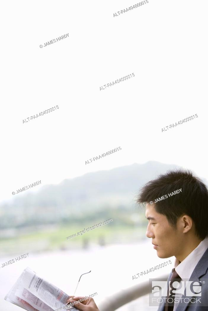 Stock Photo: Businessman holding newspaper and glasses.