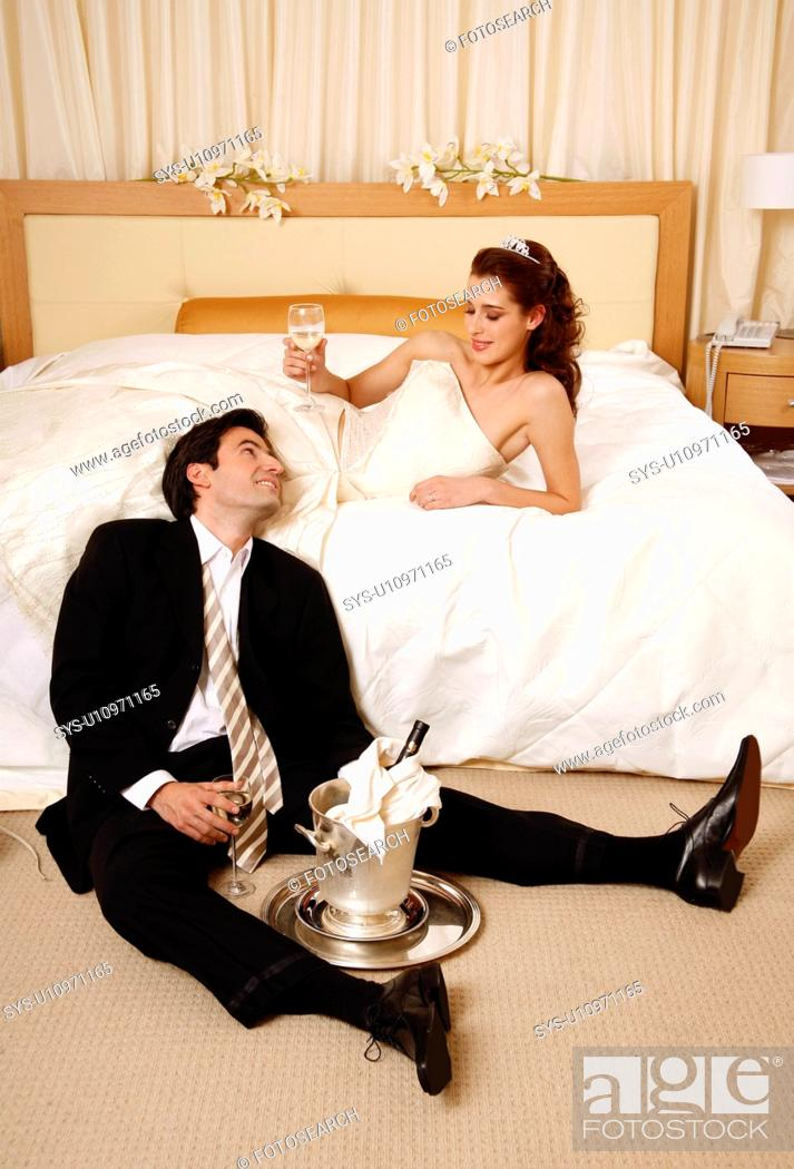 Stock Photo: Bride and groom toasting in hotel room.