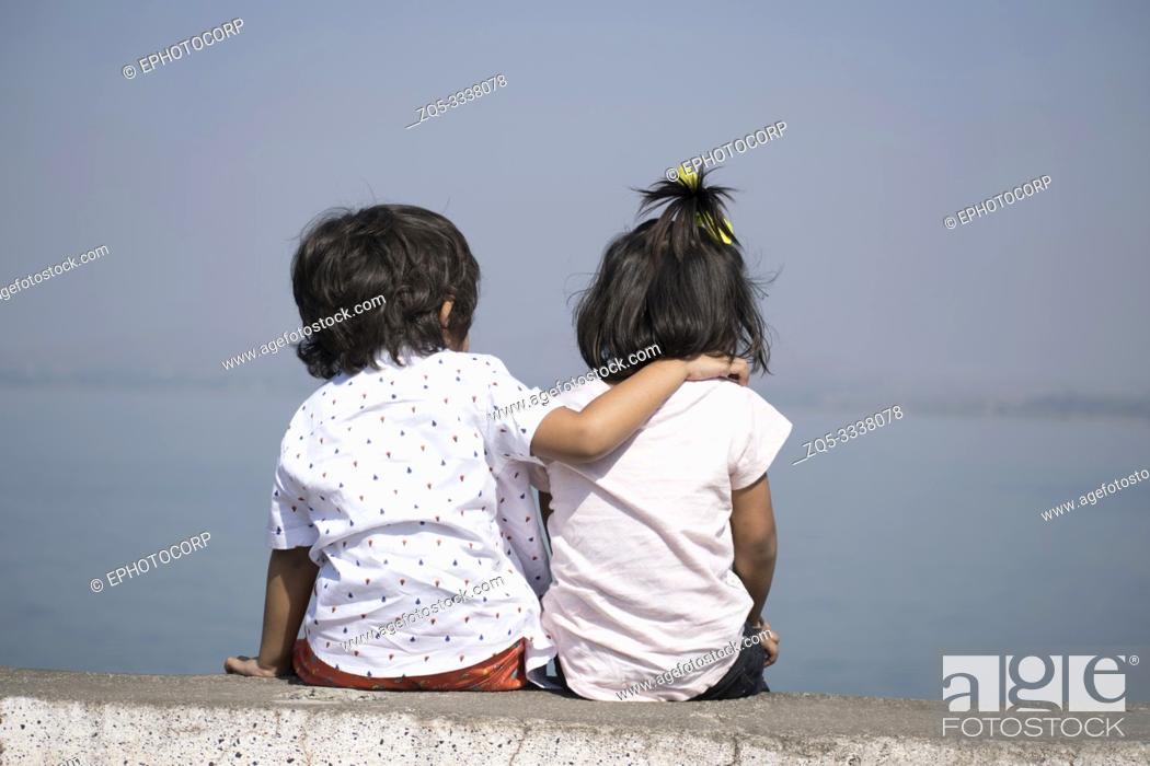 Stock Photo: Boy and little girl sitting near lake, Veer dam, Pune, Maharashtra, India.