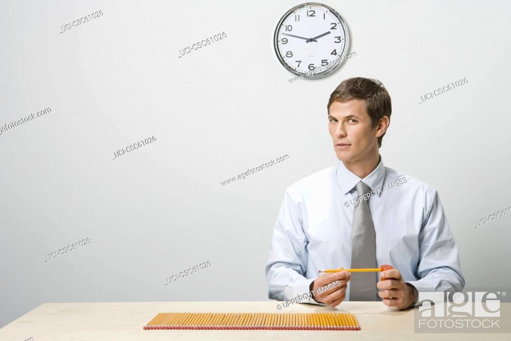 Stock Photo: Businessman next to row of pencils.