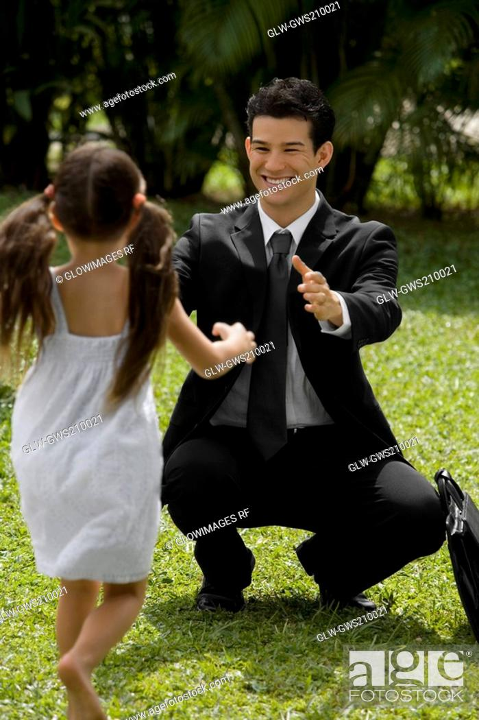 Stock Photo: Young man looking at his daughter and smiling.
