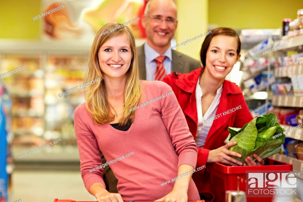 Stock Photo: Germany, Cologne, Man and women in supermarket, smiling, portrait.