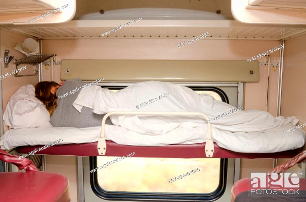 Stock Photo: Passenger train sleeping on the top shelf of the side seats in the second-class carriage turned to the wall.