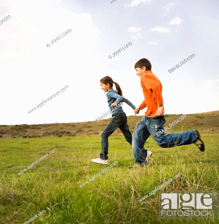 Stock Photo: Hispanic sister and brother running in field.