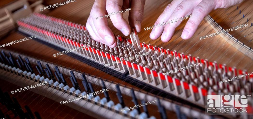 "Stock Photo: 22 June 2020, Mecklenburg-Western Pomerania, Rostock: Instrument maker Johann-Gottfried Schmidt uses the Springer in the workshop """"Historical Keyboard."