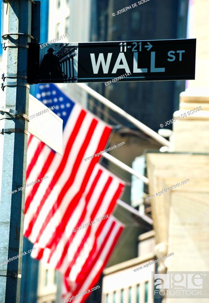 Stock Photo: Wall Street sign with the New York Stock Exchange building and American flags in the background in the financial district in New York City.