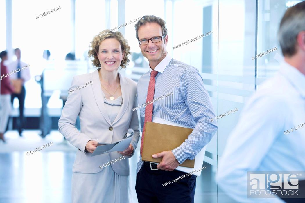 Stock Photo: Business people smiling in office hallway.