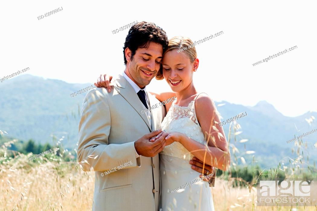 Stock Photo: Newlyweds in field looking at wedding ring.