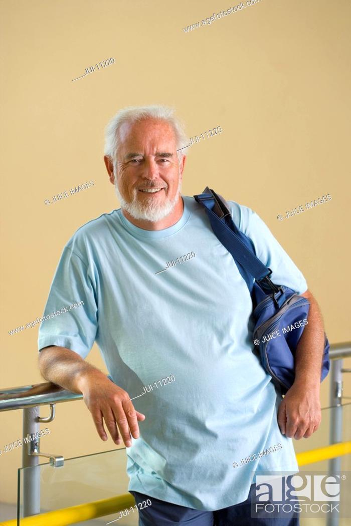 Stock Photo: Senior man with gym bag over shoulder, leaning on railing, smiling, portrait.