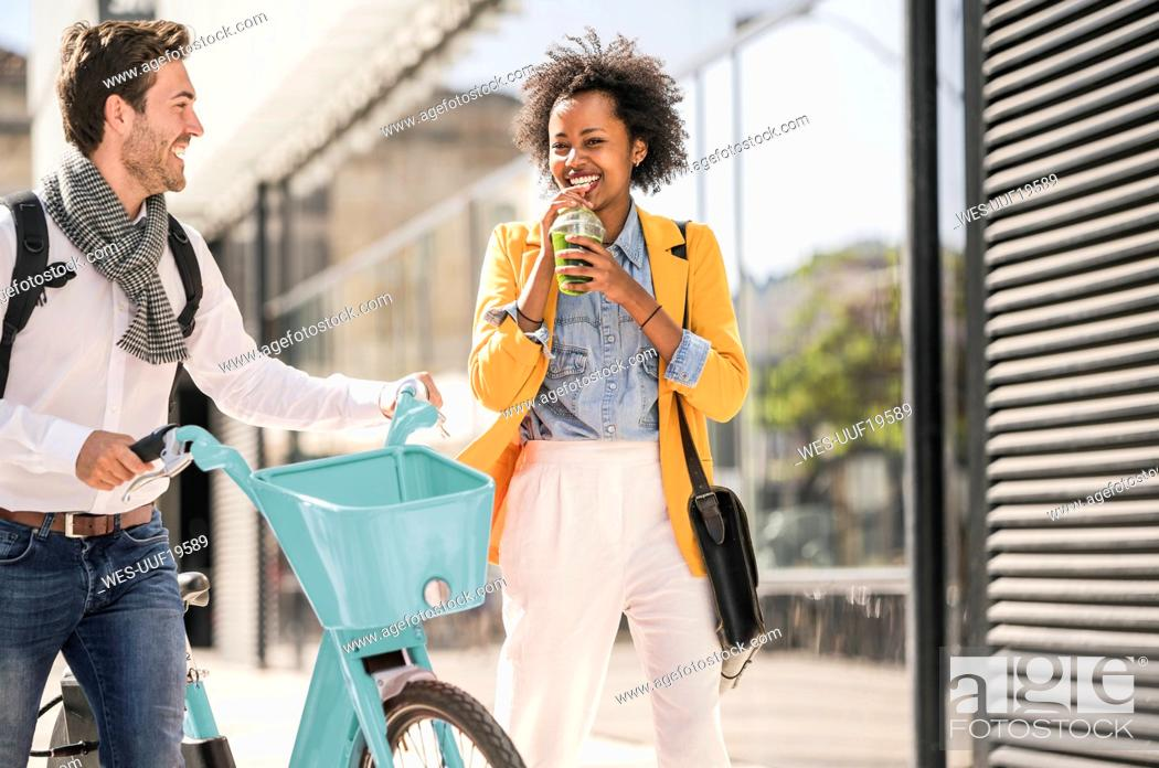 Stock Photo: Happy young man and woman with bicycle in the city on the go.