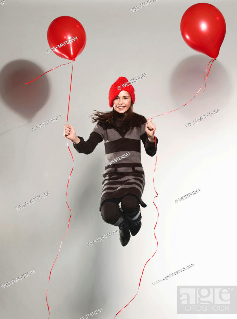 Stock Photo: Girl 10-11 holding balloon and jumping.
