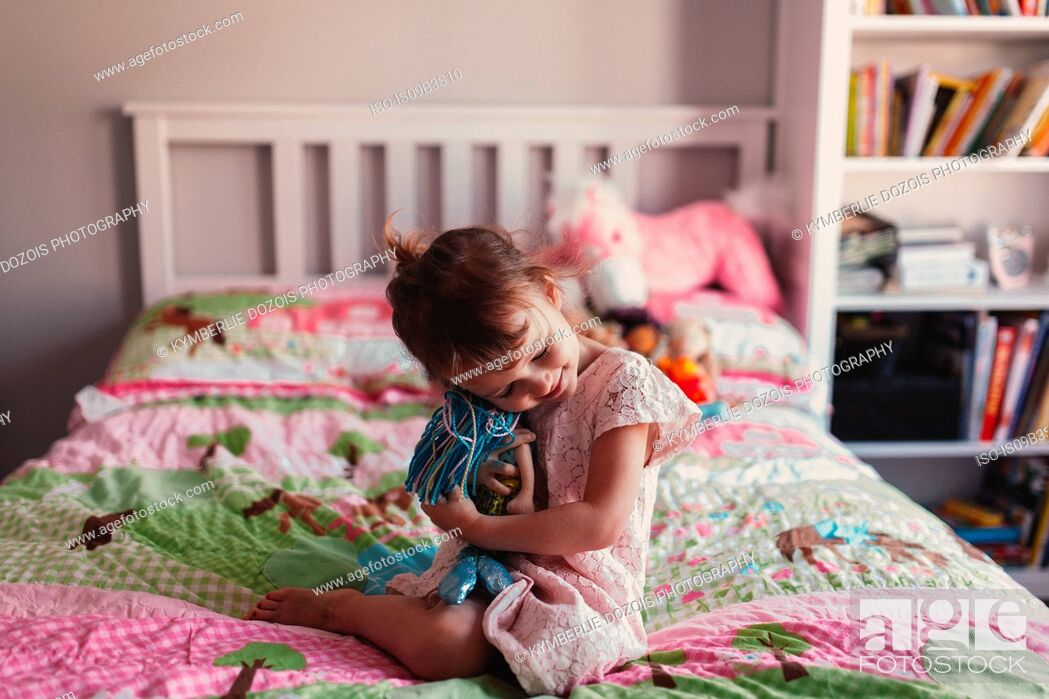 Stock Photo: Girl sitting on bed hugging rag doll.