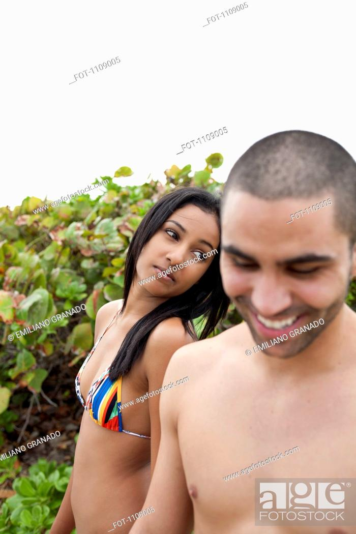 Stock Photo: A young man teasing his girlfriend at the beach.