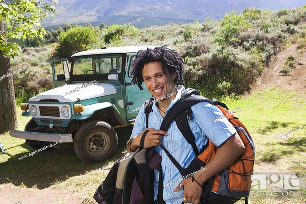Stock Photo: Young man unloading parked jeep at start of camping holiday, carrying rucksacks, smiling, portrait.
