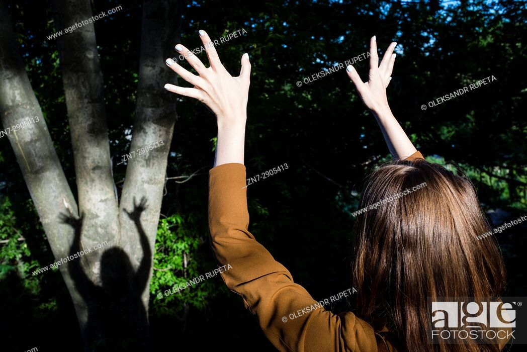Stock Photo: A woman looking at her shadow on a tree.