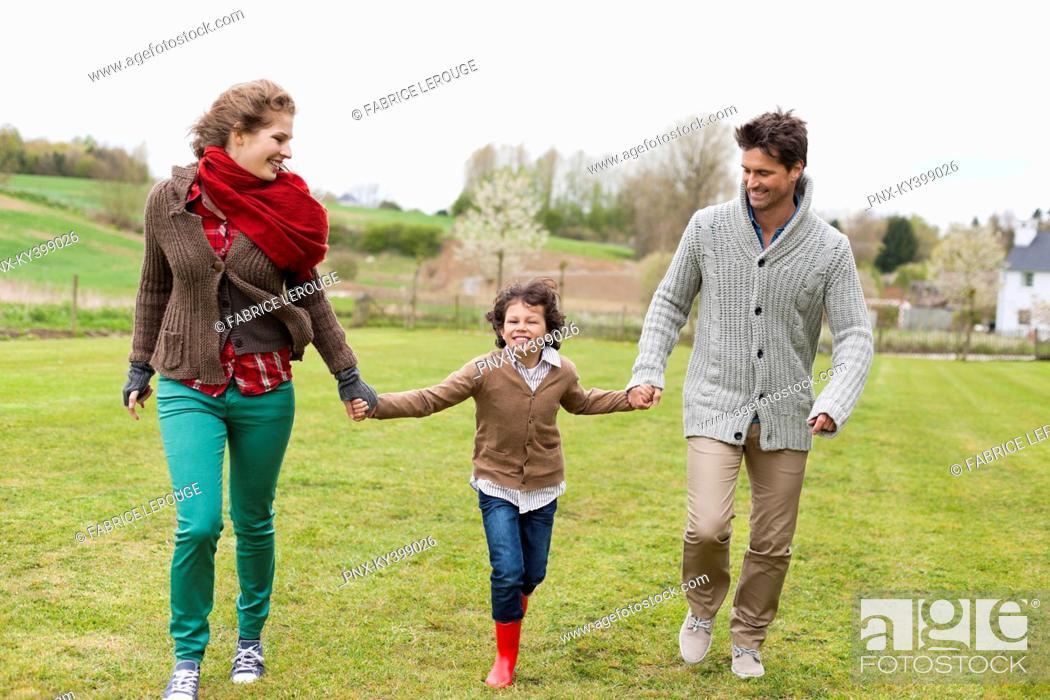 Stock Photo: Happy family walking in a field.