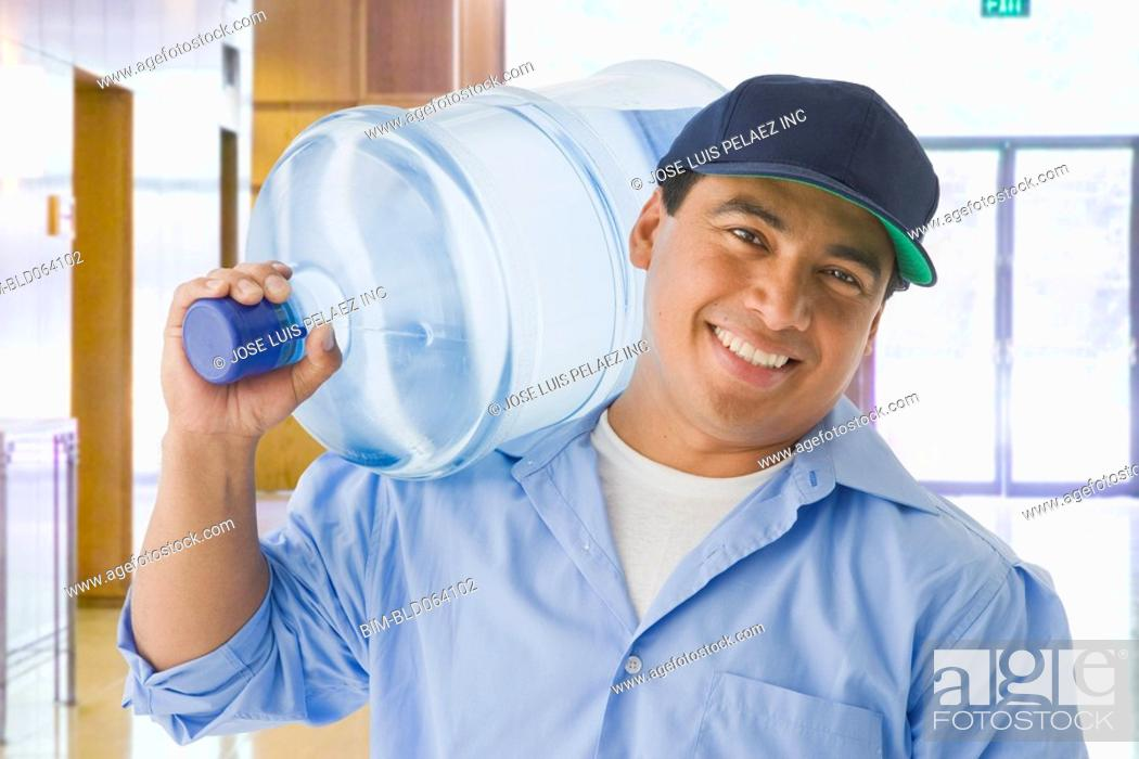 Stock Photo: Hispanic delivery man carrying large water bottle.