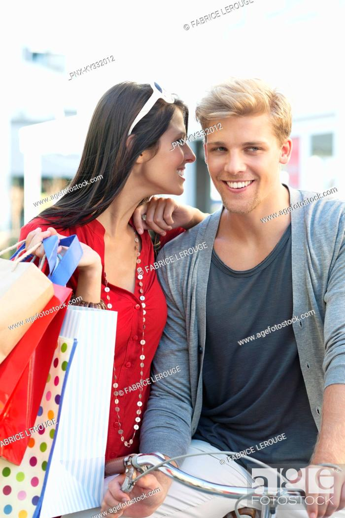 Stock Photo: Young man on bicycle with his girlfriend whispering in ear.