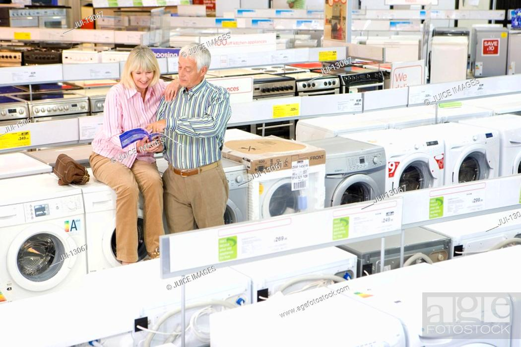 Stock Photo: Mature couple shopping for appliances, looking at brochure.