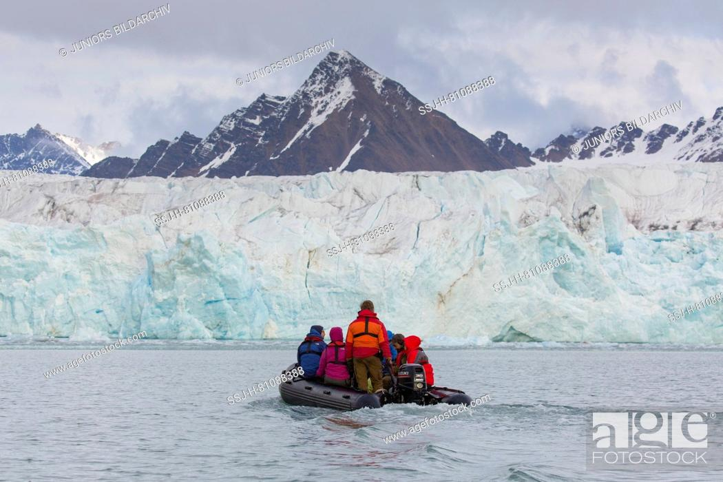 Stock Photo: Tourists in an inflatable boat in front of Fjortende Julibreen glacier (July 14th Glacier) on the Krossfjorden, Spitsbergen, Norway.