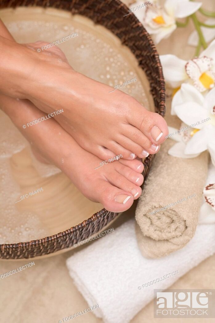 Stock Photo: Woman enjoying a soothing foot bath.
