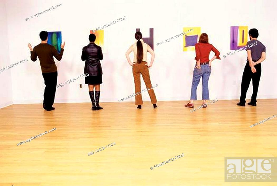 Imagen: Group of people looking at paintings in an art gallery.