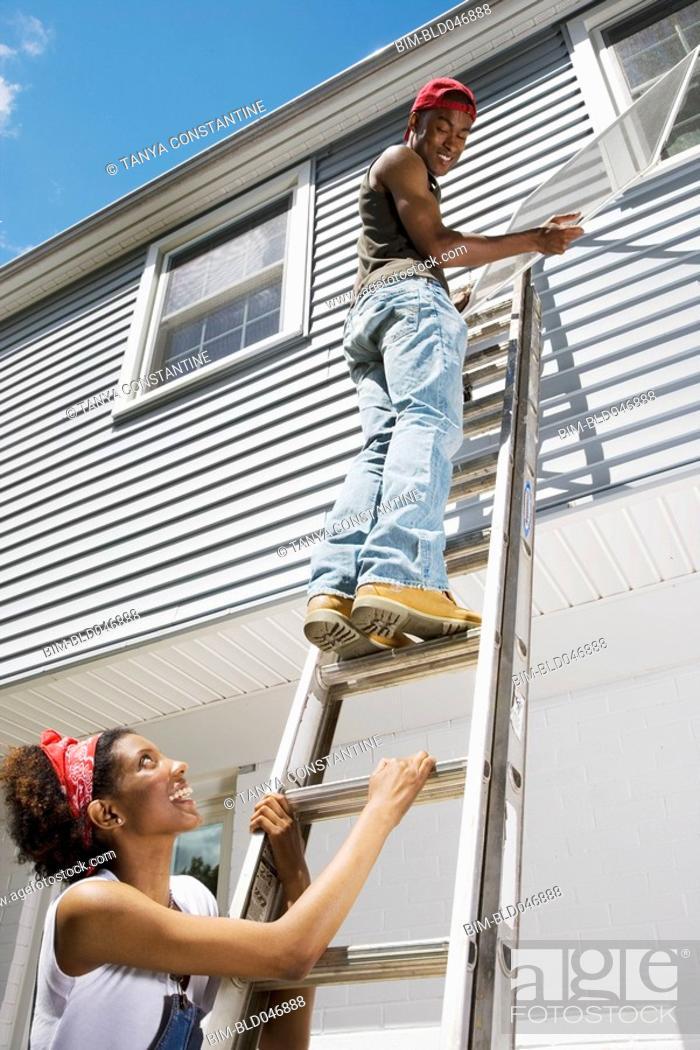 Stock Photo: African American couple replacing window screens.