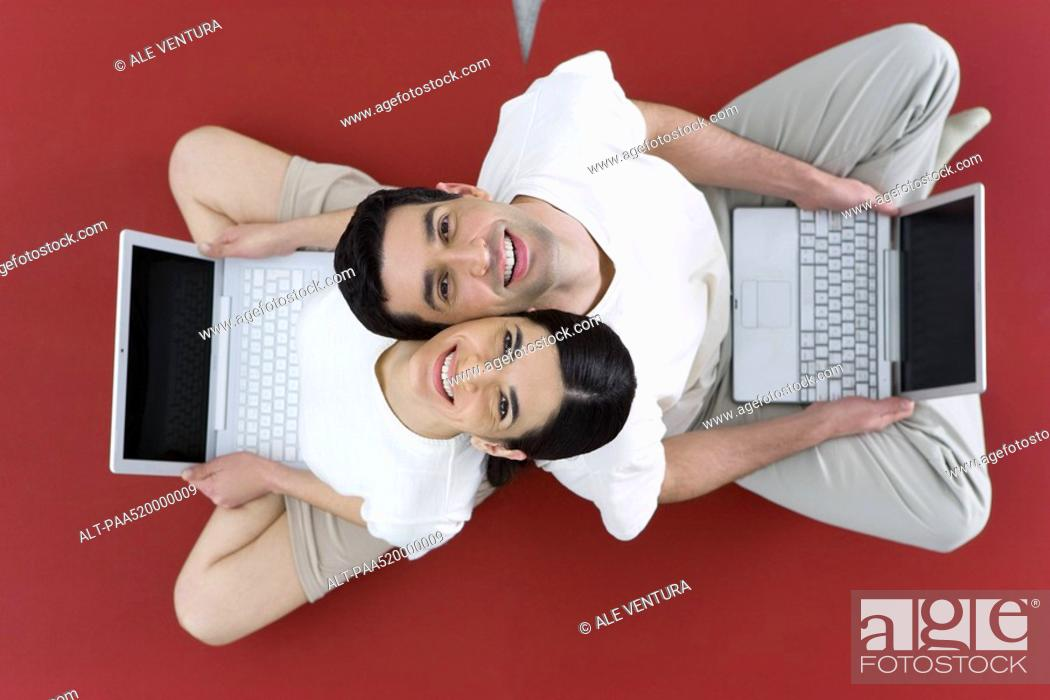 Stock Photo: Couple sitting back to back on the ground, holding laptop computers, smiling up at camera.