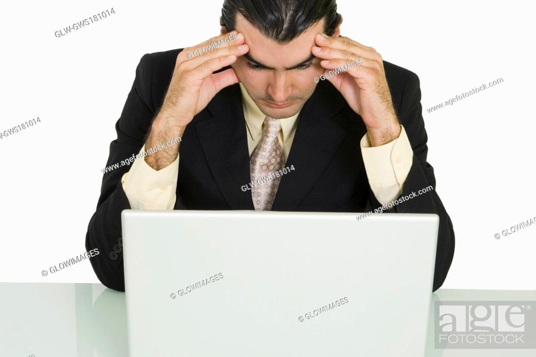 Stock Photo: Close-up of a businessman sitting in front of a laptop with his head in his hands.