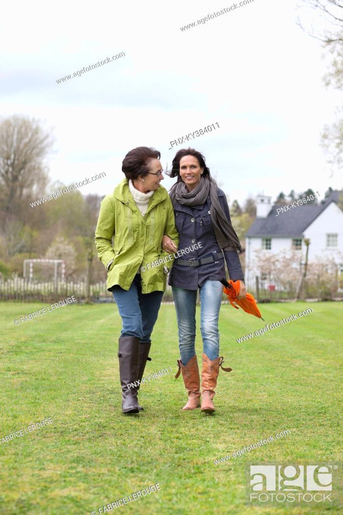 Stock Photo: Two women walking in a lawn.