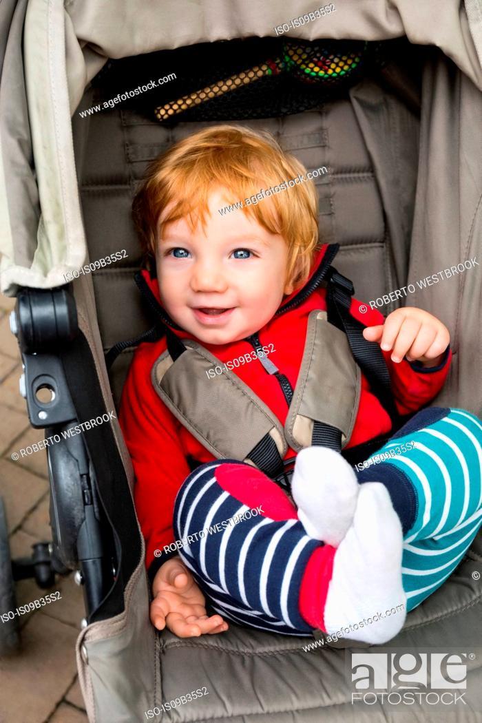 Stock Photo: Toddler sitting in pushchair, smiling.
