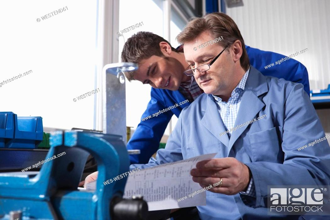 Stock Photo: Germany, Neukirch, Apprentice and instructur reading documents, portrait.