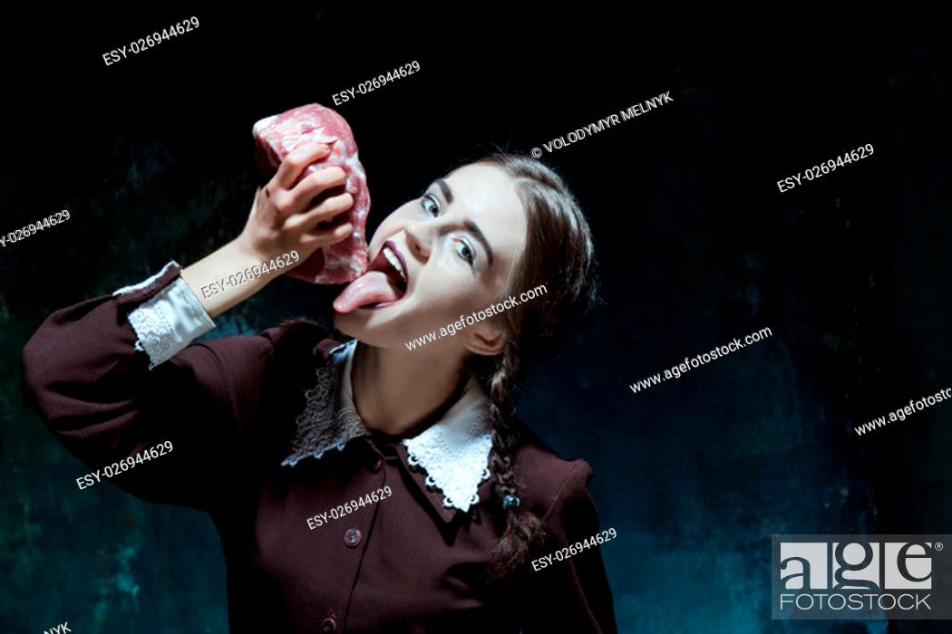 Stock Photo: Portrait of a young girl with a piece of raw meat. Girl in school uniform as killer. The image in the style of Halloween.