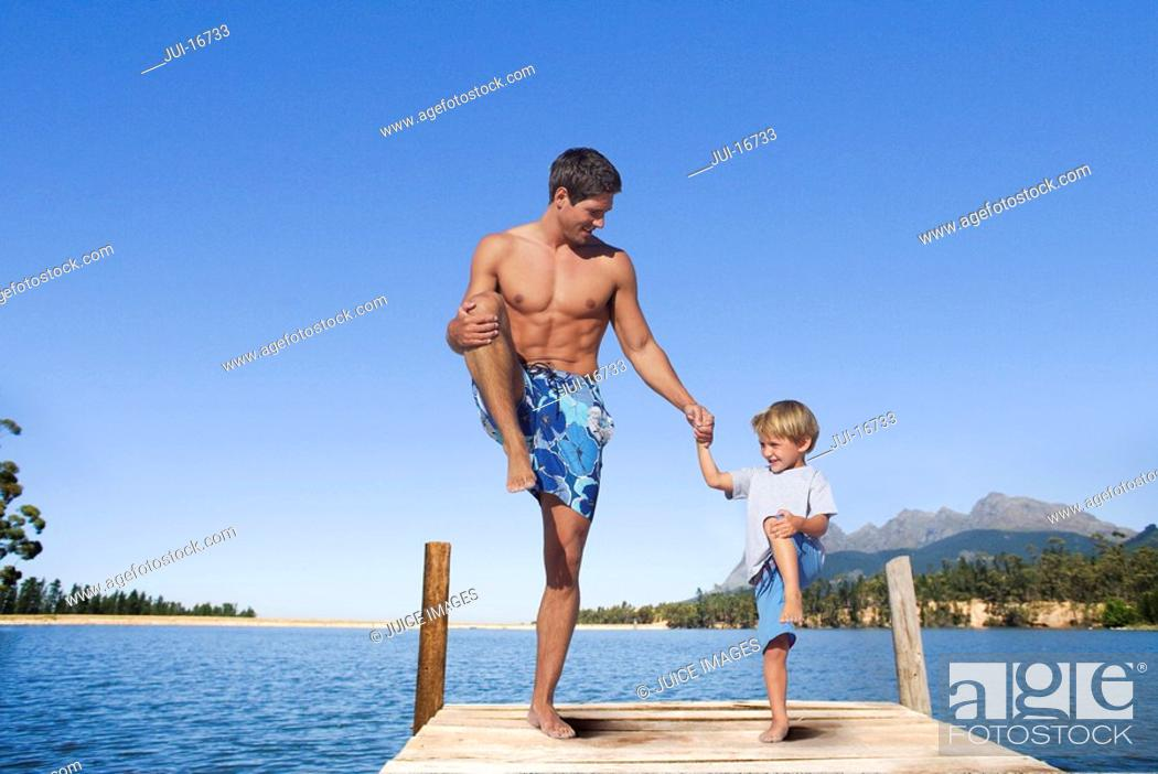 Stock Photo: Father and son balancing in lake dock.