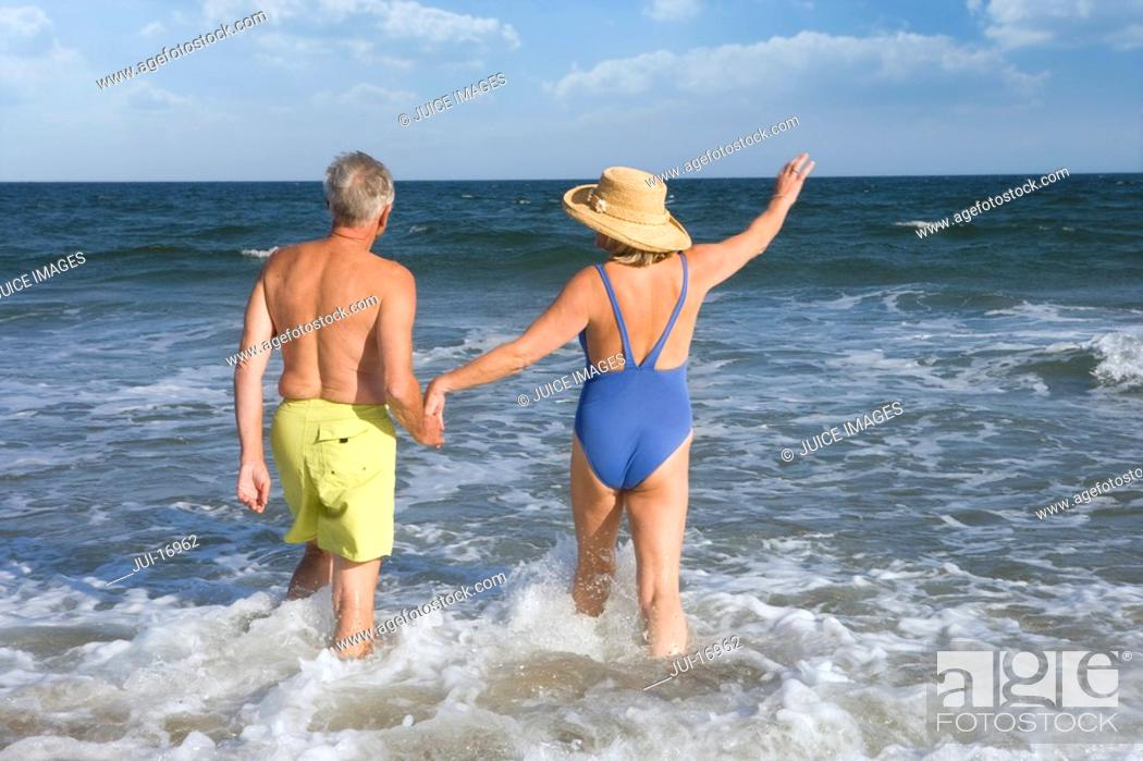 Stock Photo: Senior couple walking in sea, rear view.