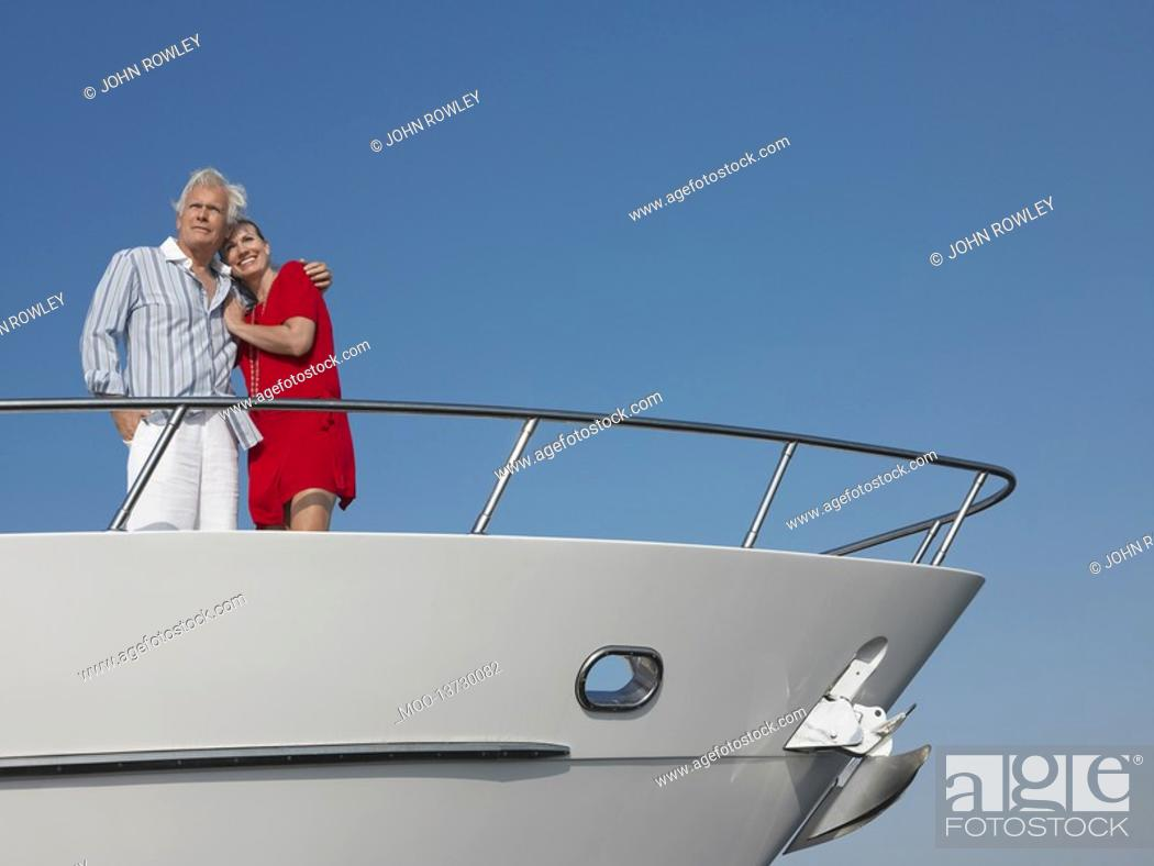 Stock Photo: Middle-aged couple standing in bow of yacht.