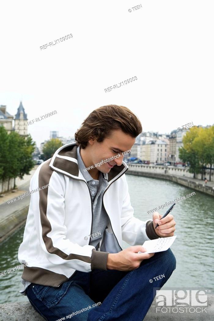 Stock Photo: Young man sitting on Pont Neuf bridge, writing postcard, Paris, France.