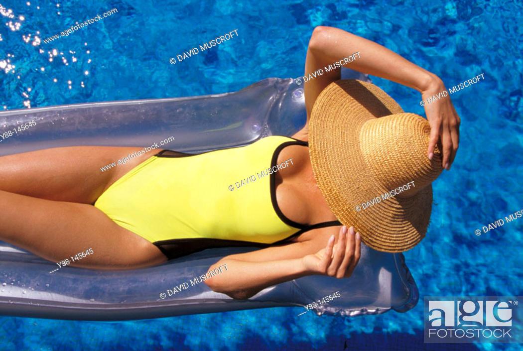 Stock Photo: Woman sunbathing on airbed.