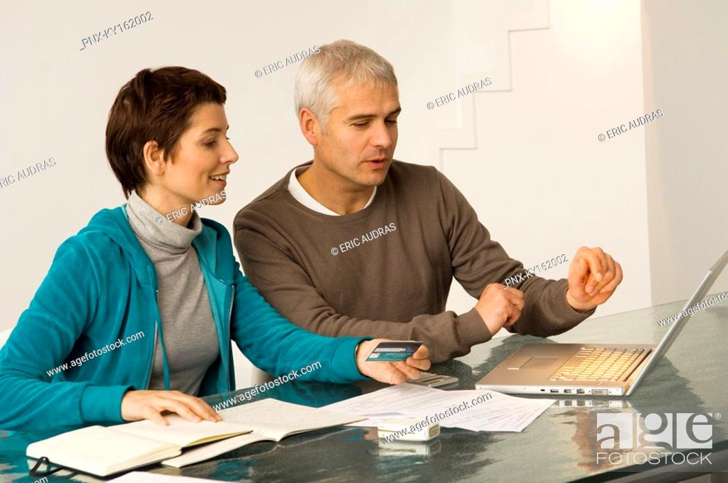 Stock Photo: Mature man and a mid adult woman working on a laptop and holding a credit card.