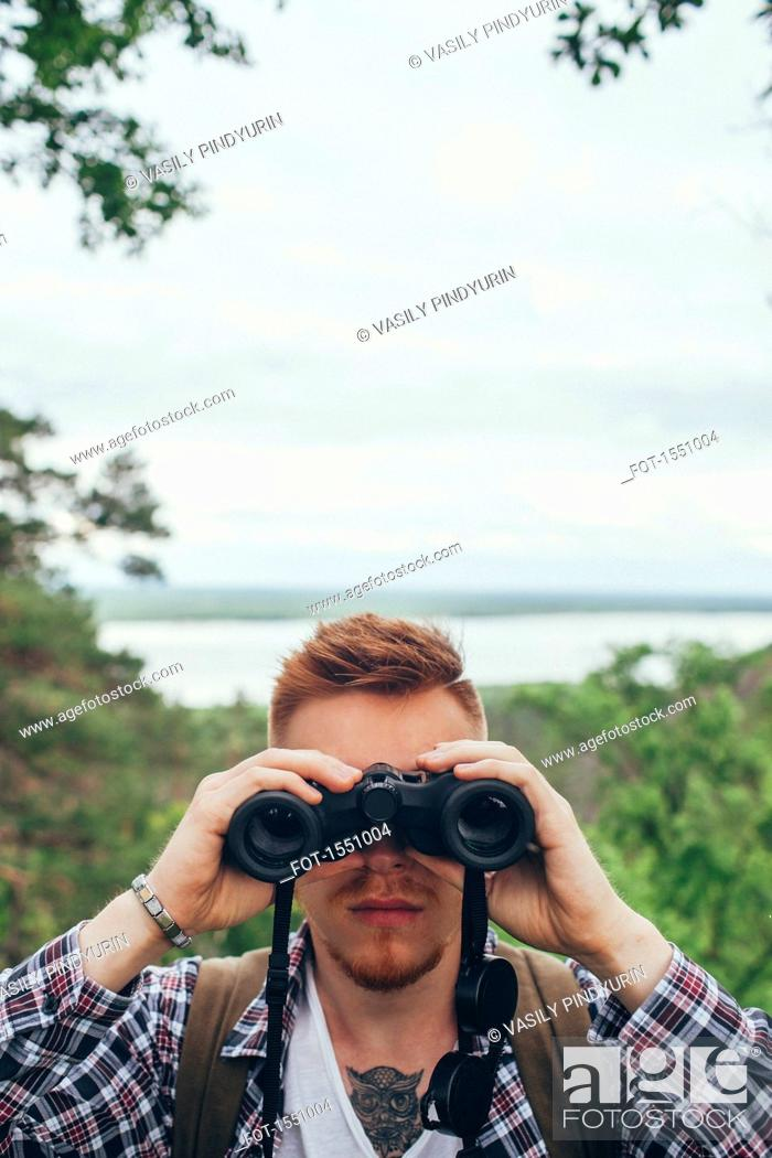 Imagen: Close-up of young man with binoculars hiking at forest against sky.